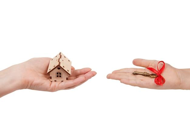 片方の手のひらにもう一方の手のひらにある木造の家は、孤立した白い壁に赤い弓が付いた鍵