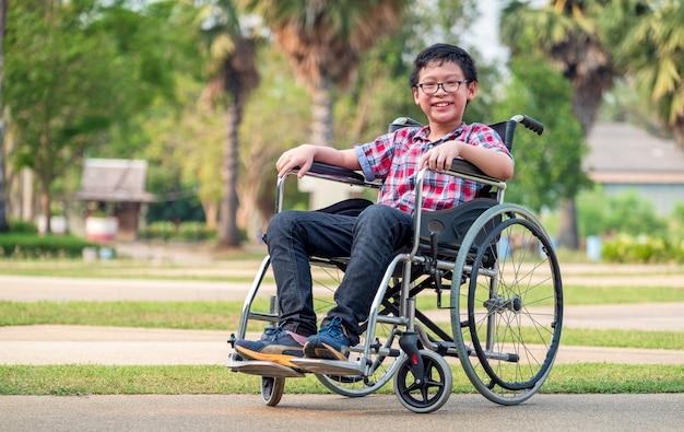 公園では、車椅子の子供。彼のハンドルをよく見てください。健康で幸せな障害児の概念である医療の概念。