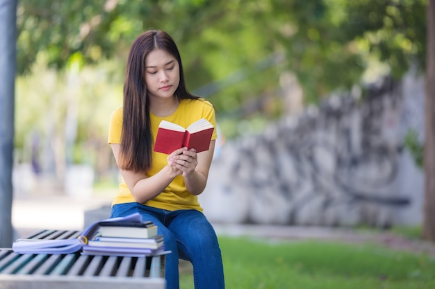 В парке счастливая брюнетка сидит на скамейке и читает книгу.