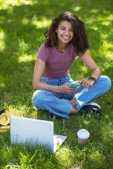 В парке. красивая девушка в розовой футболке сидит на траве в парке и учится