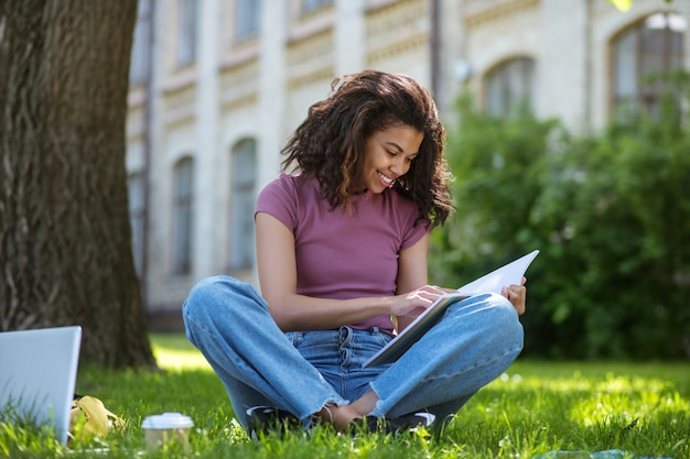 В парке. красивая девушка в розовой футболке сидит на траве в парке и учится Premium Фотографии