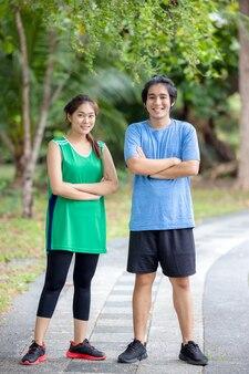 В парке молодая пара бегунов позирует портрету. спорт и любовь как концепция