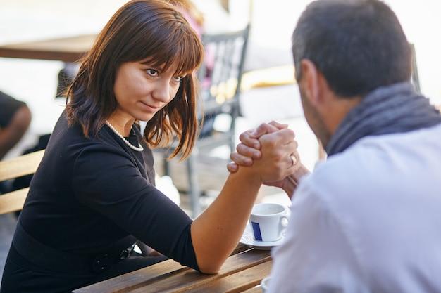 写真では、男性と女性が腕のレスリングで競います