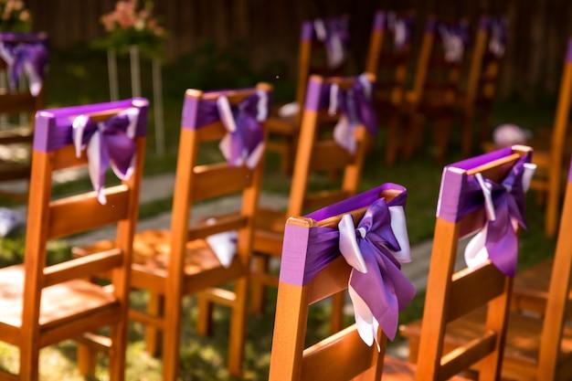 На фото мы видим стулья, украшенные бледно-лиловыми лентами. свадебная церемония на открытом воздухе