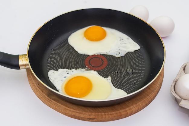 新鮮な卵で朝食を準備する過程で。フライパンで2個の卵から目玉焼き。