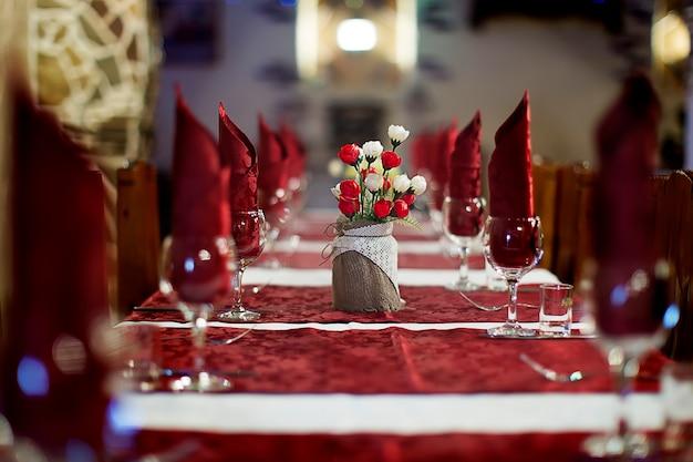 レストランでは、テーブルクロスで覆われたテーブルの上に食器があります