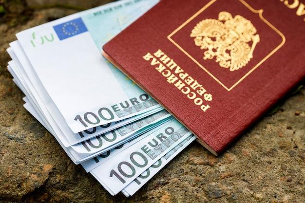 В российском паспорте лежит пачка евро, лежащая на улице. фото высокого качества