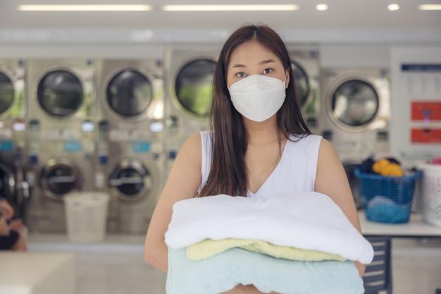 건조기가 있는 셀프 서비스 세탁실에서 한 젊은 여성이 깨끗한 다림질을 하고 있습니다.