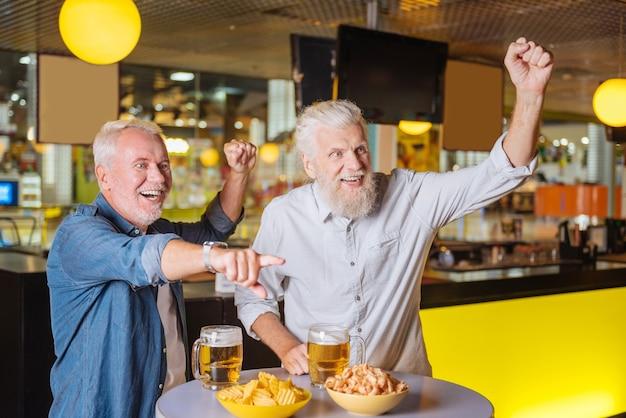 В спорт-баре. радостные счастливые мужчины смотрят футбол во время отдыха в спорт-баре