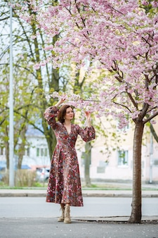 Весной женщина идет по цветущей улице с деревьями сакуры. девушка в длинном шелковом элегантном винтажном платье гуляет среди цветущих деревьев