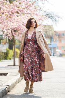 春になると、桜の木が咲き乱れる通りを女性が歩きます。長いシルクのエレガントなヴィンテージドレスを着た女の子が花の木々の間を歩きます