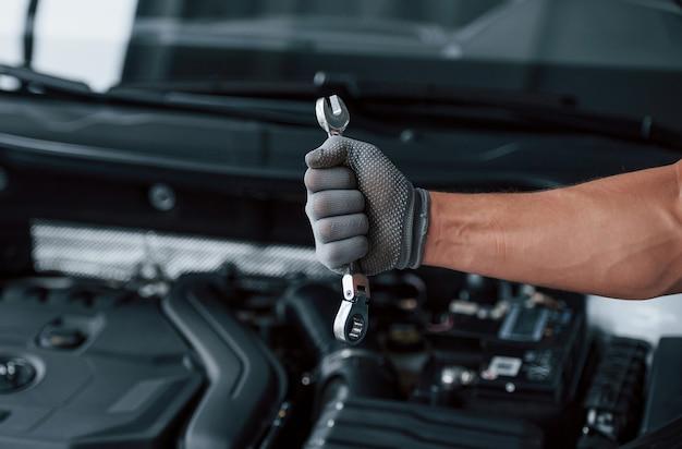 強い手に。壊れた自動車の前にレンチを保持します。