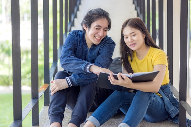 В университетском городке две азиатские пары сидят на лестнице, подняв вверх большие пальцы руки, и работают на ноутбуках.
