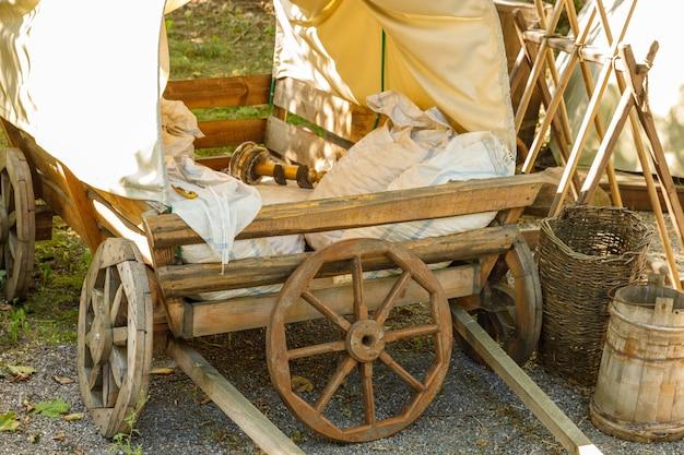 В деревне стоит старая деревянная повозка с навесом. в ярком солнечном свете