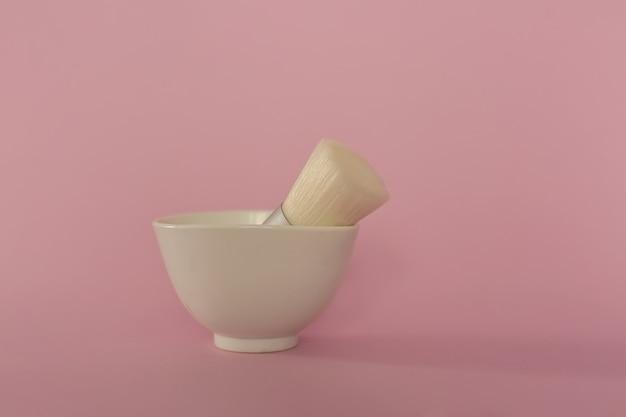 흰색 컵에는 메이크업 브러쉬가 있습니다.