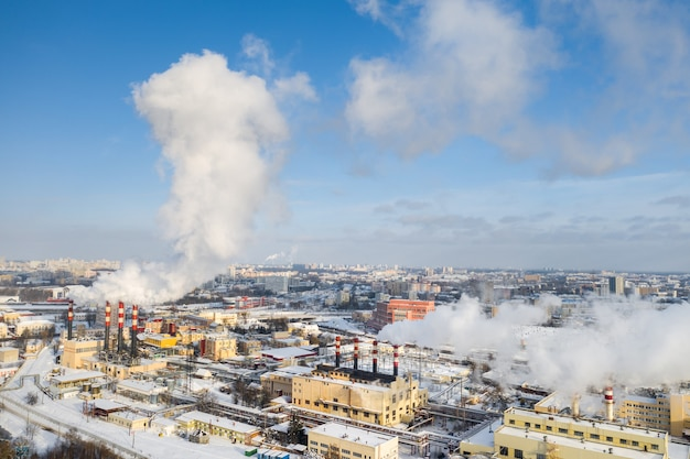 겨울 도시에는 공장 굴뚝이 담배를 피우고 있습니다. 대기 오염의 개념. 산업 폐기물에 의한 환경 오염.