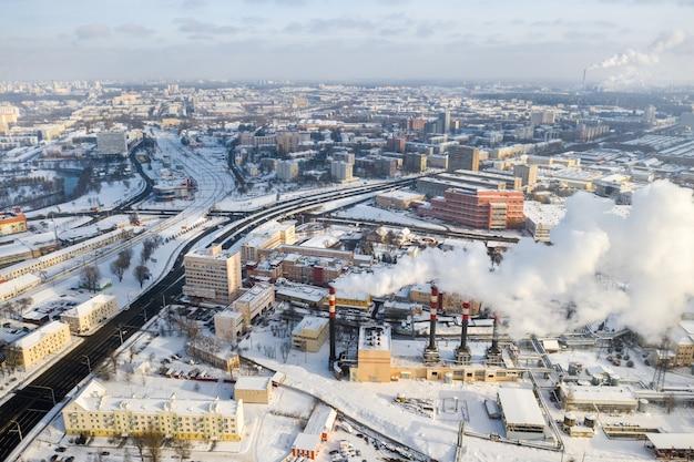 冬の街では、工場の煙突が喫煙しています