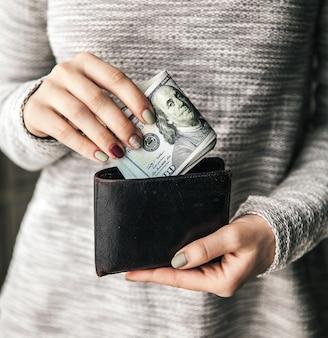 女性の手には、百ドルの札束が付いた茶色の革の財布があります。ビジネスオファー。美しいマニキュア