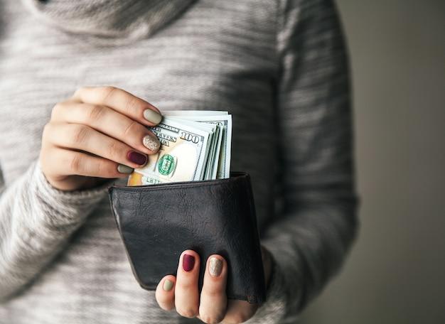 女性の手には、100ドルの札束が入った茶色の革の財布があります。ビジネスオファー。美しいマニキュア