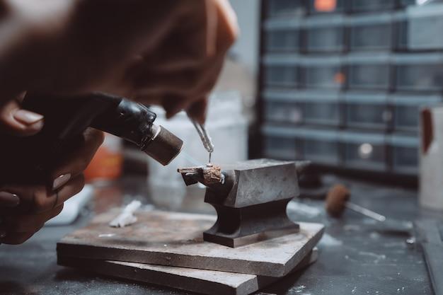 В мастерской женщина-ювелир занята пайкой ювелирных изделий