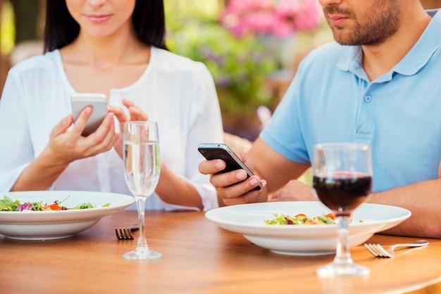 В своих отдельных мирах. крупным планом молодая пара что-то набирает на своих смартфонах во время отдыха в ресторане на открытом воздухе вместе