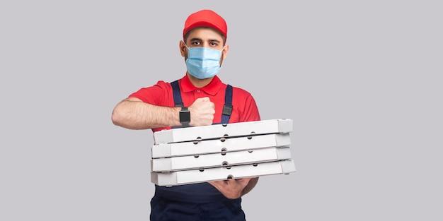 検疫で時間通りに配達!灰色の背景に段ボールのピザボックスのスタックを保持し、立っている制服と赤いtシャツの外科医療マスクを持つ男。屋内、スタジオショット、隔離、コピースペース