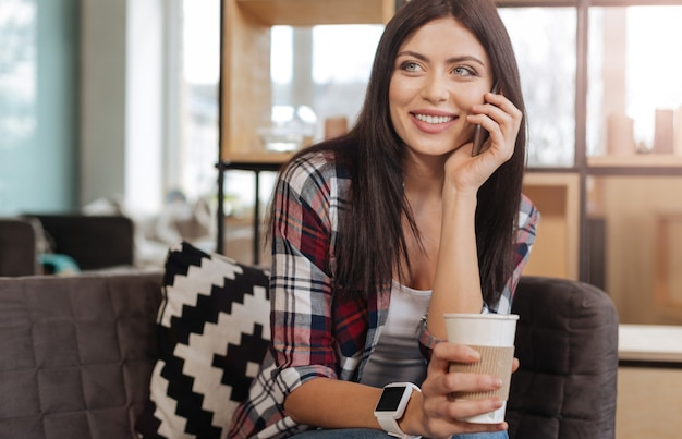 На связи. веселая, довольная привлекательная женщина разговаривает с кем-то по телефону и пьет чай в хорошем настроении
