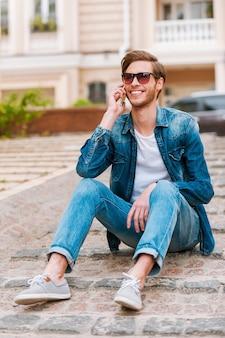 彼の友達と連絡を取り合う。屋外に座って携帯電話で話している自信のある若い男