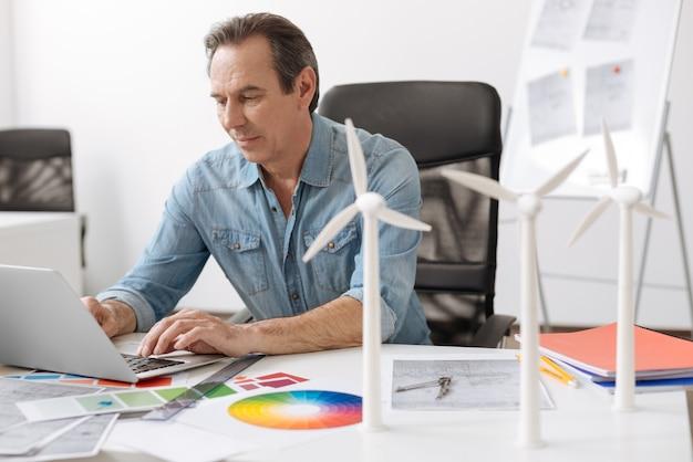 세계와 연락합니다. 풍력 터빈 건설 프로젝트에서 작업하는 동안 테이블에 앉아 노트북을 사용하는 긍정적 인 수석 엔지니어