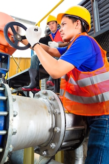 В коммунальном хозяйстве или на заводе технические специалисты или инженеры, работающие над клапаном, на строительном техническом оборудовании или на промышленной площадке.