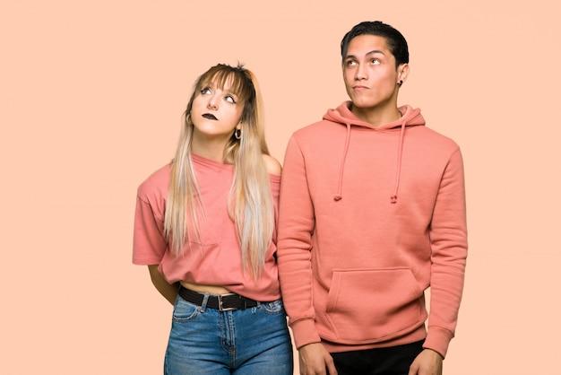 В день святого валентина молодая пара смотрит с серьезным лицом на розовом фоне