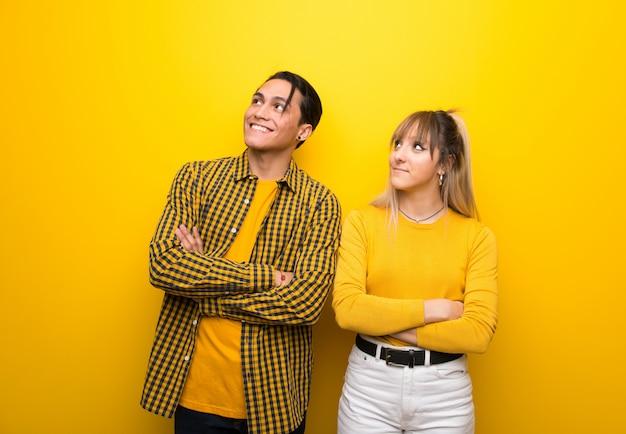 В день святого валентина молодая пара на яркий желтый фон, глядя вверх, улыбаясь