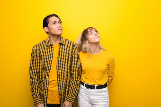 В день святого валентина молодая пара на яркий желтый фон, глядя с серьезным лицом