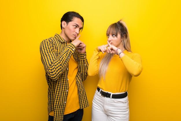 バレンタインの日に沈黙のジェスチャーの兆しを見せ鮮やかな黄色の背景に若いカップル