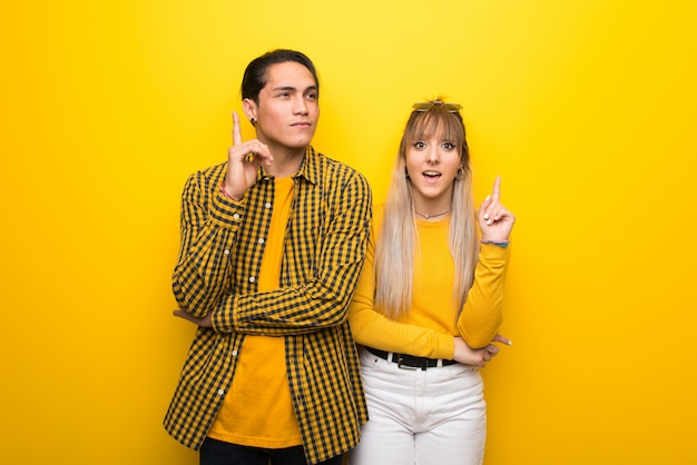 В день святого валентина молодая пара на ярком желтом фоне, думая, идея, указывая пальцем вверх