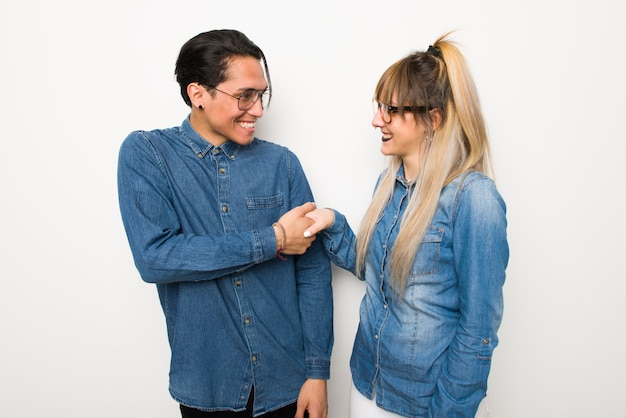 В день святого валентина молодая пара в очках рукопожатие после хорошей сделки