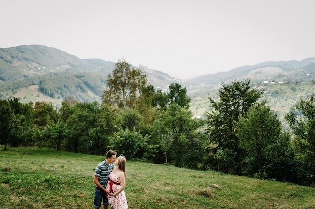 В ожидании ребенка. счастливая семья. беременная женщина с любимым мужем целуется, держит руку вокруг живота на траве. искренние нежные моменты. фон, горы, леса, природа, девять месяцев.