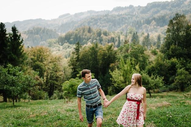 В ожидании ребенка. счастливая семья. беременная женщина с любимым мужем гуляет по траве. круглый живот. родительство. искренние нежные моменты, улыбки. муж держит жену за руку. горы, леса
