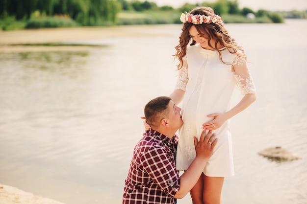 待っている赤ちゃんに。愛する夫と妊娠中の女性は湖の近くに立ちます。丸い腹。ひざまずく夫は妻に丸い腹を抱きしめます。親子関係。誠実な入札の瞬間。