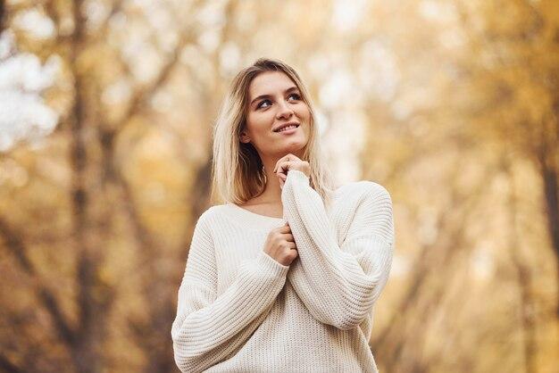 В теплой одежде. портрет молодой брюнетки в осеннем лесу в дневное время.