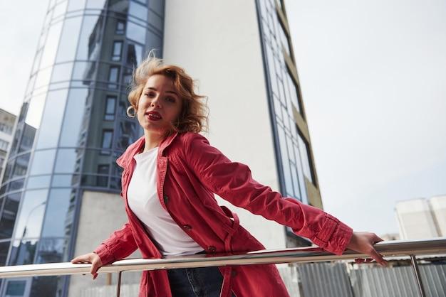 白いシャツ。暖かい赤いコートを着た大人のきれいな女性が彼女の週末の時間に街を歩いている