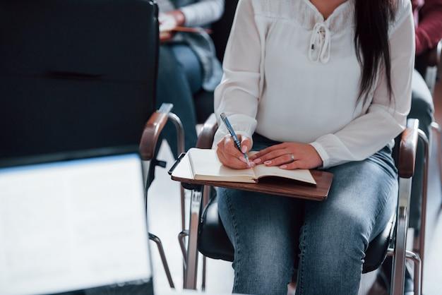 白いシャツとジーンズ。昼間の近代的な教室でのビジネス会議での人々のグループ