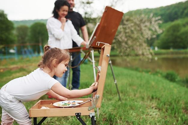 白いシャツ。祖母と祖父は孫娘と屋外で楽しんでいます。絵画の構想