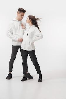 白で。白いスタジオの壁に分離されたトレンディなファッショナブルなカップル。