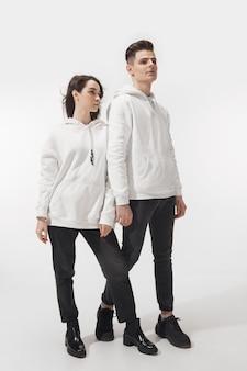 白で。白い壁に隔離されたトレンディなファッショナブルなカップル。基本的な最小限のユニセックスの服でポーズをとる白人の女性と男性。関係、ファッション、美しさ、愛の概念。包括的。