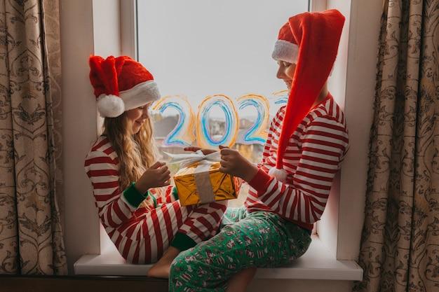 Зимой дети сидят у окна. дети ждут рождества. мальчик и девочка в новогодних шапках сидят на подоконнике.