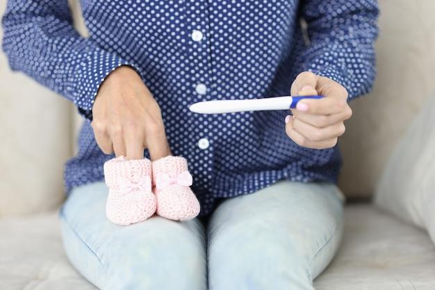В женских руках тест на беременность и маленькие детские тапочки беременность положительная новость концепция