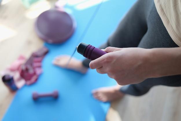 В женских руках скакалка для спорта. физические упражнения в домашних условиях