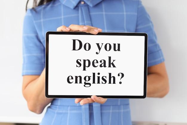碑文のある女性の手のタブレットでは、学習のための英語のモバイルアプリケーションを話します