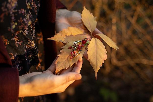 В женских руках осенний желтый листок осени и украшение для волос из стеклянных бусин.